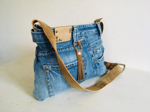 Jeanstas met geschuurd leren draagband
